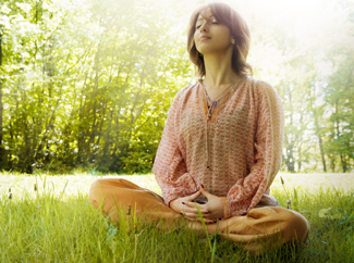 A photograph of a woman meditating.